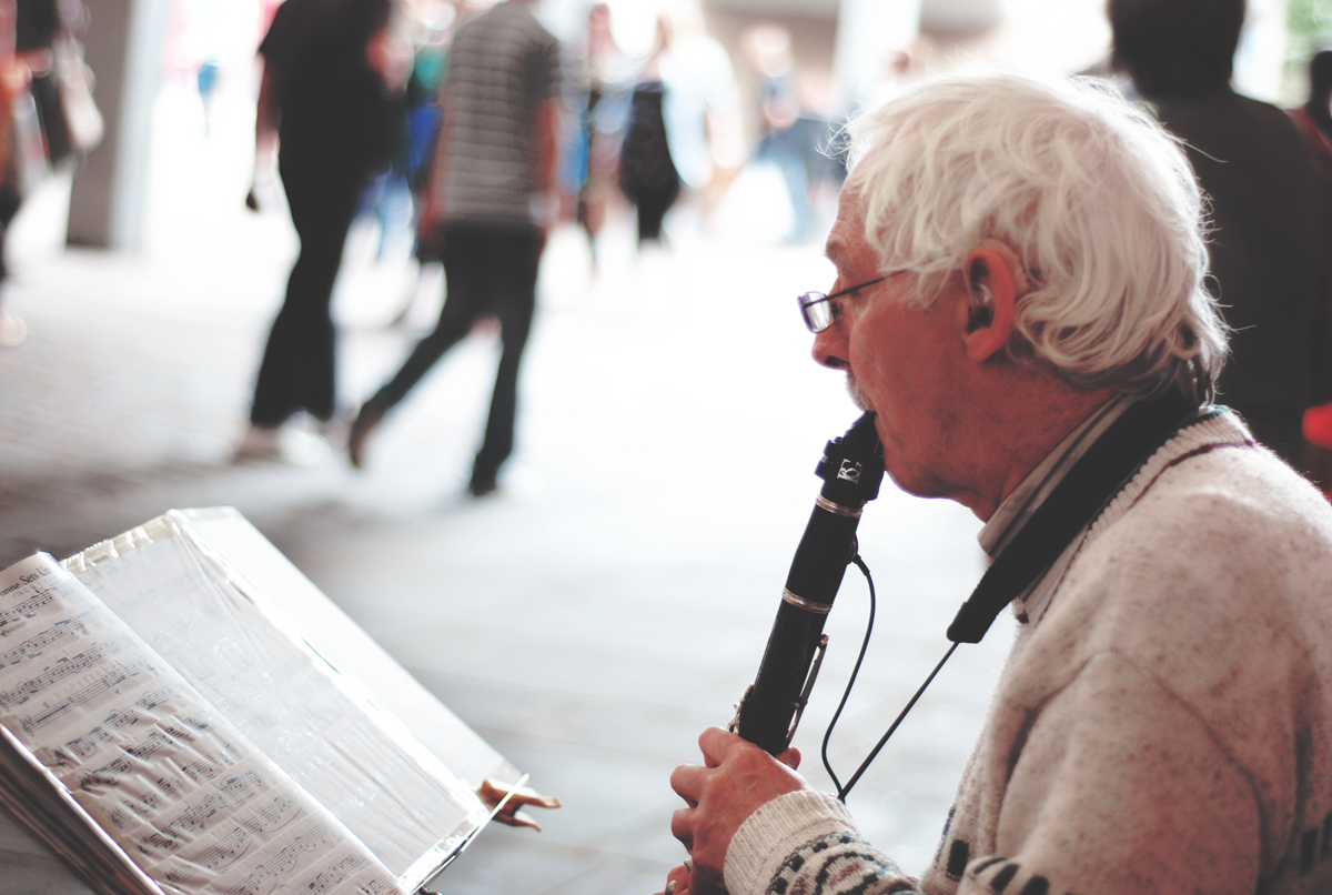 A photograph of an old man making music in the street